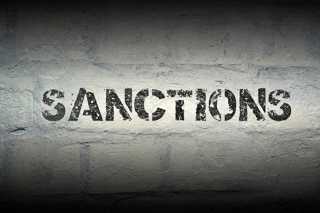 Wzornik sankcji nadrukowany na grunge białej ścianie z cegły