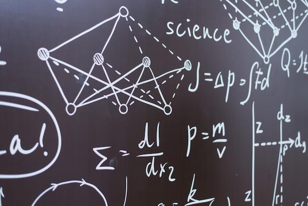 Wzory fizyczne i chemiczne oraz wykresy na czarnej tablicy szkolnej