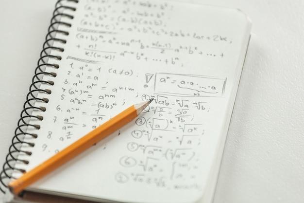 Wzory matematyczne są zapisywane ołówkiem na kartce papieru, zadania matematyczne