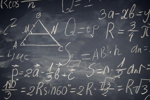 Wzory matematyczne zapisane białą kredą na czarnej tablicy, stonowanych retro