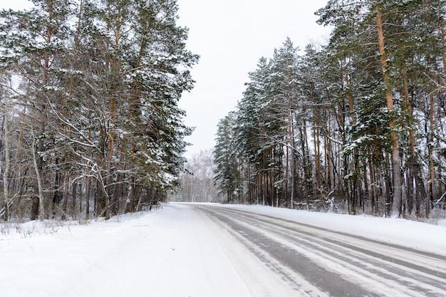 Wzory na zimowej autostradzie w postaci czterech prostych linii. śnieżna droga na tle ośnieżonego lasu. zimowy krajobraz.