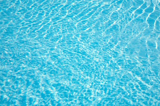 Wzory promieni słonecznych falujących na tafli wody basenowej