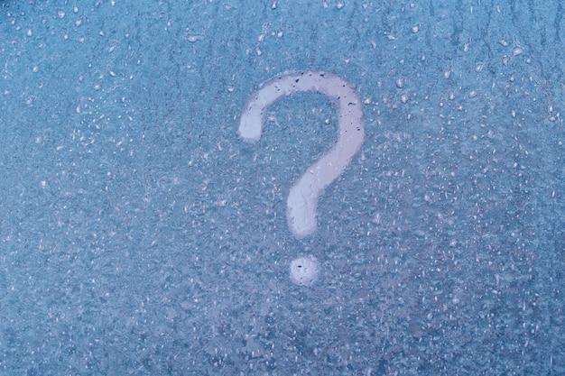 Wzory szronu na szybie okna ze znakiem zapytania w zimie, z bliska. znak zapytania na niebieskiej mrożonej szybie