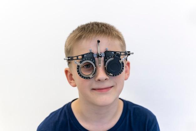 Wzrok chłopca jest sprawdzany okulista sprawdza wzrok dziecka sprzęt okulisty włączony
