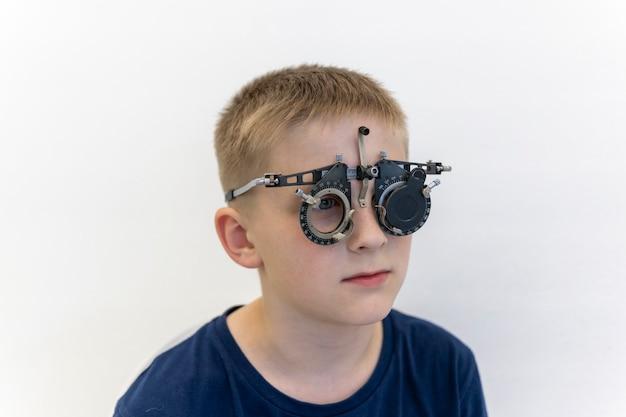 Wzrok chłopców jest sprawdzany za pomocą narzędzi optometrystycznych na białym tle