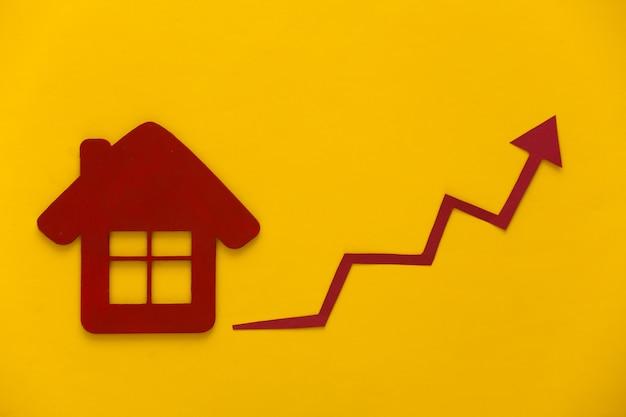 Wzrost cen mieszkań. figurka domu i strzałka wzrostu zmierzająca w górę na żółto