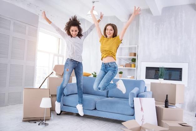 Wzrost emocji. przyjemne, wesołe dziewczyny wskakują radośnie do nowego mieszkania, świętując razem przeprowadzkę do nowego wspólnego mieszkania