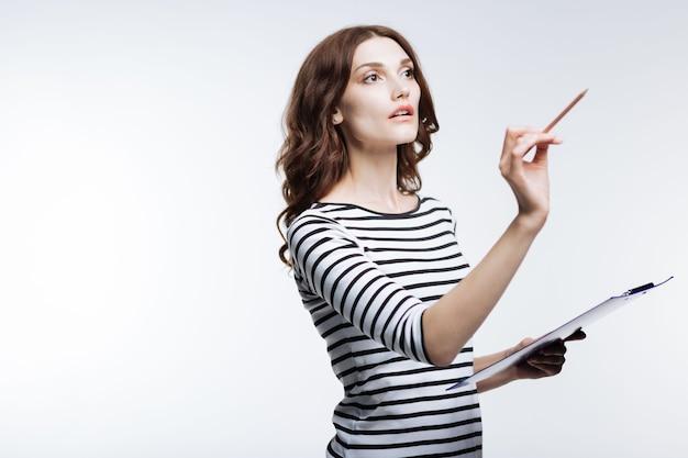 Wzrost inspiracji. przyjemna młoda kobieta w pasiastym swetrze pisze w powietrzu ołówkiem, trzymając w drugiej ręce uchwyt na prześcieradło