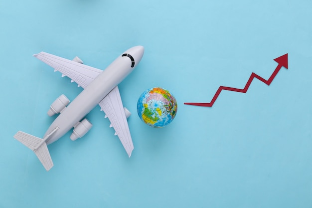 Wzrost podróży lotniczych. samolot z kulą ziemską, strzałka wzrostu ma tendencję do podnoszenia się na niebiesko