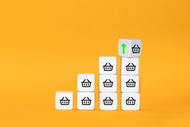 Wzrost wielkości sprzedaży sprawia, że biznes się rozwija. sześcian obraca się ze strzałką i symbolem koszyka. pomysł na biznes.