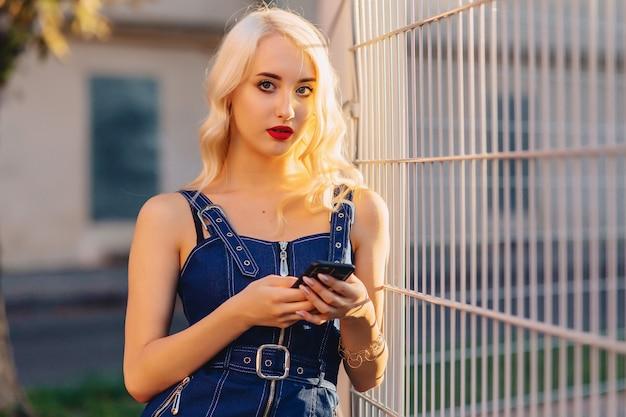 Wzruszająca blond atrakcyjna dziewczyna w okularach przeciwsłonecznych z telefonem w lato świetle słonecznym miastowym