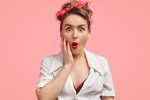 Wzruszająca kobieta pinup z oszołomioną miną, zdumiona nagłymi wiadomościami, szeroko otwiera usta, nie może uwierzyć w błąd, odizolowana na różowej ścianie