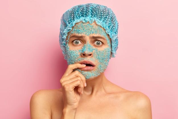 Wzruszająca niezadowolona kobieta patrzy z nieszczęśliwym wyrazem twarzy, trzyma palec na ustach, słyszy złe wieści od kosmetyczki, nakłada odżywczą maskę z błękitnej soli morskiej