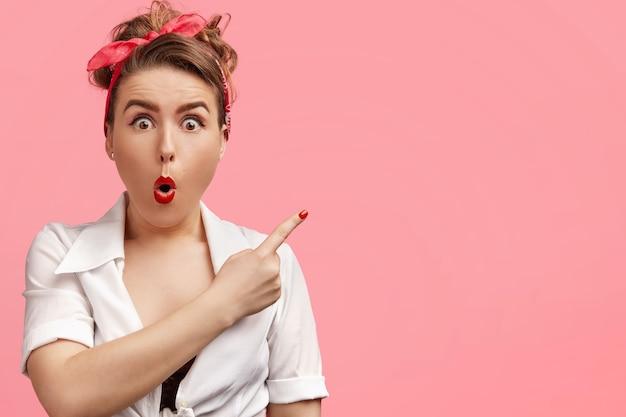 Wzruszająca oszołomiona kobieta w stylu retro ma zdumiony wyraz twarzy, wskazuje palcem wskazującym w prawym górnym rogu.