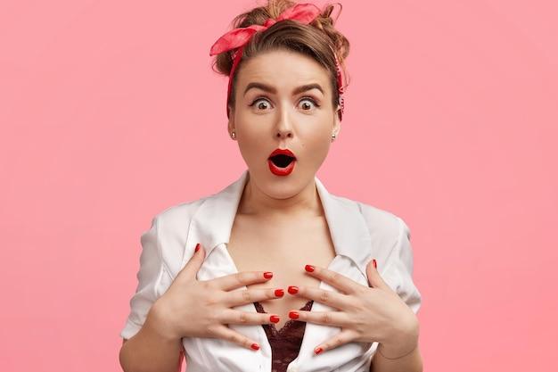 Wzruszająca piękna dama trzyma ręce na piersi, wpatruje się w coś z zapartym tchem, nie może uwierzyć w coś niesamowitego, nosi czerwoną opaskę, ma pomalowane na czerwono usta i manicure, odizolowane na różowo