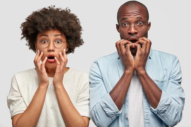 Wzruszająca, zszokowana, ciemnoskóra para afroamerykanów wygląda z nerwowo przestraszonymi minami, trzymaj ręce blisko ust, wpatruj się w usta, reaguj na nagłe, niespodziewane wiadomości, stań razem w domu