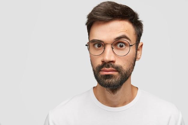 Wzruszający brodaty młody chłopak z grubym zarostem, modną fryzurą, wygląda ze zdziwieniem