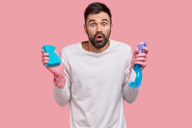 Wzruszający nieogolony mężczyzna z przerażoną miną, trzyma butelkę detergentu i gąbkę, wykonuje prace domowe, bierze udział w wiosennych porządkach