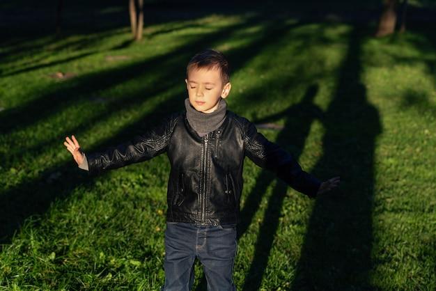 Wzruszający portret chłopca w wieku przedszkolnym z otwartymi rękoma i zamkniętymi oczami małe dziecko cieszące się zabawą