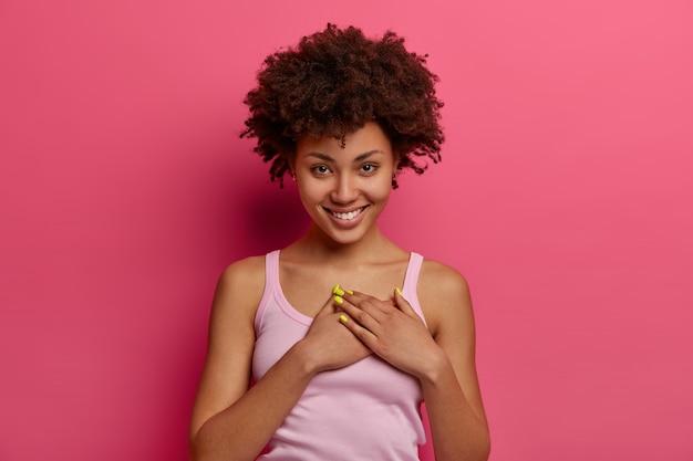 Wzruszona, zadowolona, urocza kobieta słyszy wzruszającą historię, przykłada dłonie do serca, czuje wdzięczność, obiecuje, uśmiecha się delikatnie, nosi zwykłe ubranie, ceni miły prezent, pozuje na różowej ścianie.