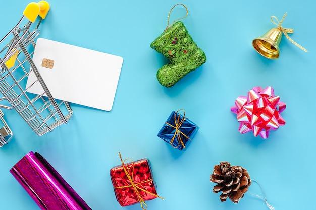Xmas ornamenty z pustą kredytową kartą i wózek na zakupy na błękitnym tle dla bożych narodzeń d