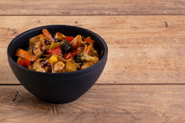 Yakissoba z kurczaka w czarnej ceramicznej misce na drewnianym stole.