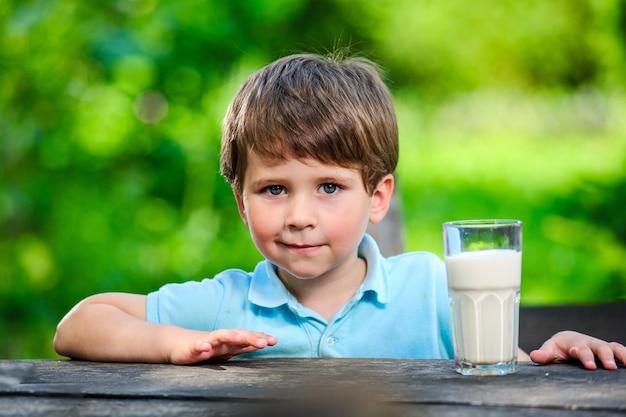 Yang mały i słodki chłopiec na zdjęciu ze szklanką mleka.