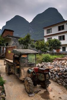 Yangshuo, guangxi, chiny zużyty zabytkowy traktor rolniczy stoi pod gołym niebem w chłopskiej wiosce, pośród krasowych wzgórz guilin i yangshuo, w pobliżu farmy w południowych chinach.