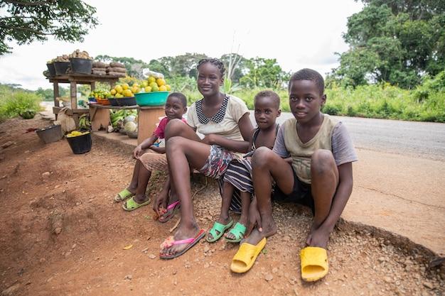 Yaounde, kamerun, 9 października 2019: grupa afrykańskiego rodzeństwa siedząca na poboczu drogi, biedna i ubrana w znoszone, stare ubrania. sprzedają jedzenie na ulicy. typowe afrykańskie dzieci.