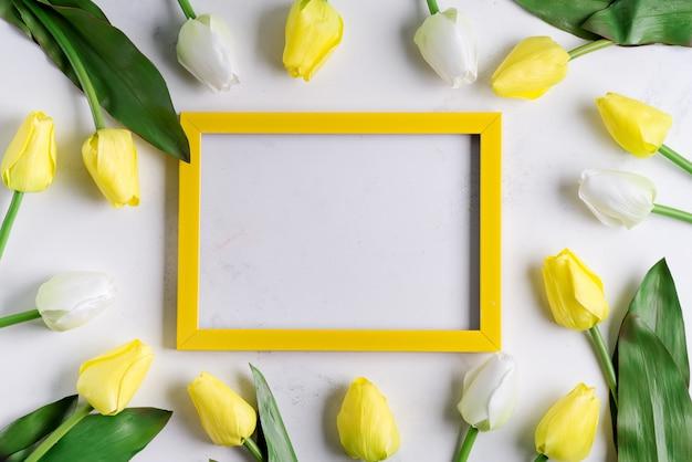 Yellowtulips z pustą obrazek ramą na bielu marmuru tle, kopii przestrzeń