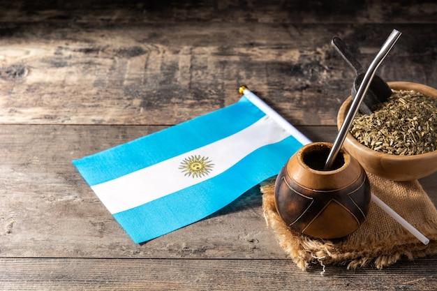 Yerba mate herbata i flaga argentyny na drewnianym stole. tradycyjny napój argentyński