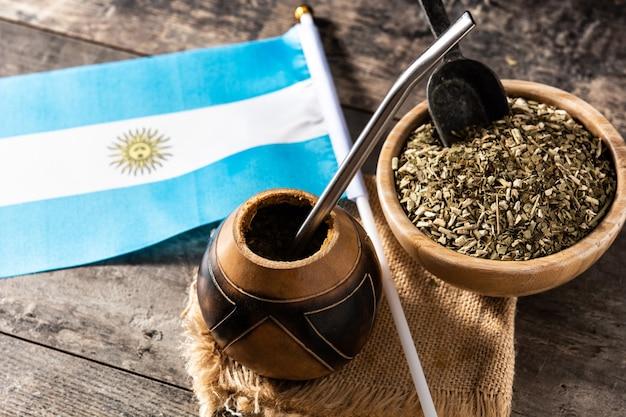 Yerba mate herbata i flaga argentyny na drewnianym stole z miejsca na kopię. tradycyjny napój argentyński