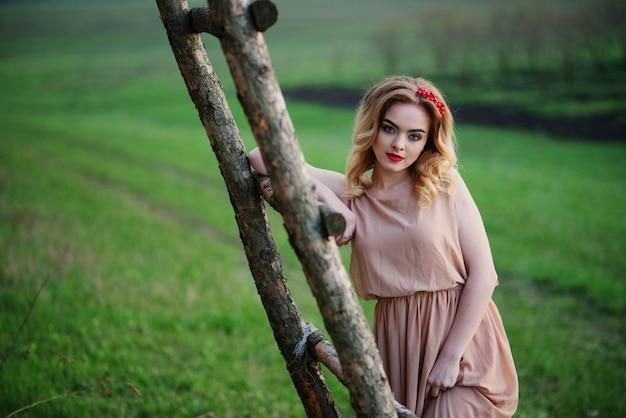 Yong elegancka blondynki dziewczyna przy róży suknią na ogrodowego tła drewnianych schodkach.