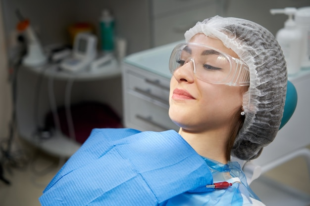 Yong ładna kobieta siedzi na fotelu dentystycznym w gabinecie dentystycznym, pacjentka u dentysty czeka na sprawdzenie