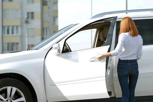 Yong ładna kobieta stojąca w pobliżu dużego samochodu terenowego na zewnątrz. kierowca dziewczyna