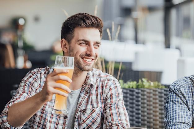 Yong piękny mężczyzna pije piwo po ciężkiej pracy