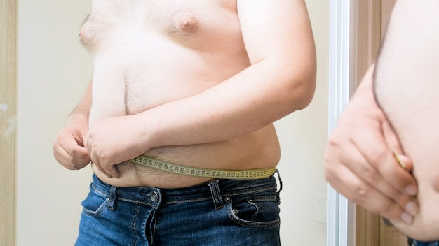 Yougn grubas pomiaru duży brzuch fet z miarką. pojęcie męskiej nadwagi, odchudzania i diety.