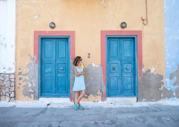 Yound blond kobieta przy typowym greckim tradycyjnym miasteczkiem z kolorowymi budynkami na wyspie kastelorizo, grecja