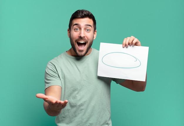 Younf przystojny mężczyzna trzyma kartkę papieru z miejsca na kopię