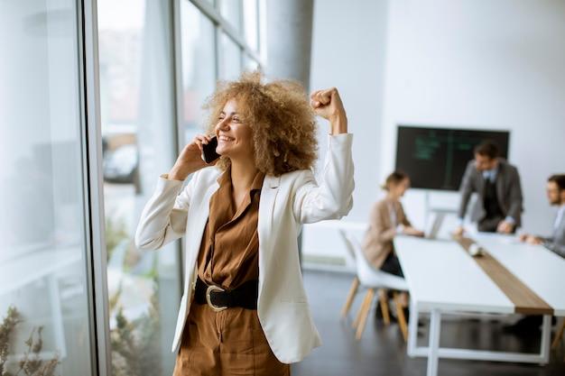 Young african american businesswoman stojącej i przy użyciu telefonu komórkowego w nowoczesnym biurze