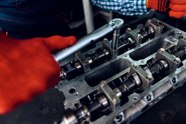 Young auto mechanic twists a nut. koncepcja stacji paliw.