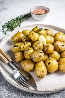 Young fresh domowe ziemniaki gotowane z tymiankiem. białe tło. widok z góry.