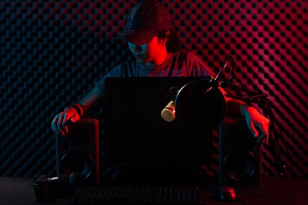 Youtuber młodych dorosłych transmitowany na żywo na kanale youtube. kobieta łączy media społecznościowe z profesjonalnym sprzętem, takim jak elektroniczna klawiatura do gier, mysz, monitor, głośnik, kamera, studio, ciemnoczerwony