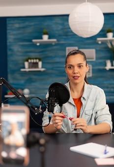 Youtuber na blogu wideo przedstawia i recenzuje produkt do makijażu w transmisji na żywo z subskrybentami internetowymi. kobieta vlogerka udostępniająca na żywo samouczek o urodzie w mediach społecznościowych
