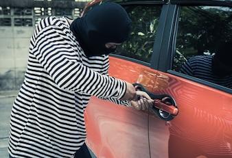 Złodzieje próbują użyć śrubokrętu otwierają drzwi samochodu, kradną samochód, gdy właściciel samochodu robi