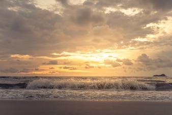 Złotego zmierzchu chmurny niebo na spokoju i czyści plażę.