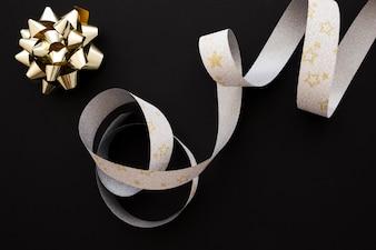 Złoty łuk i srebrny kształt gwiazdy srebrnej wstążki na czarnym tle