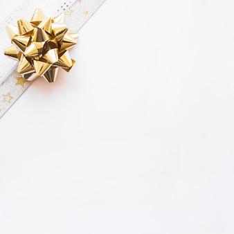 Złoty wstążka łuk na rogu białym tle