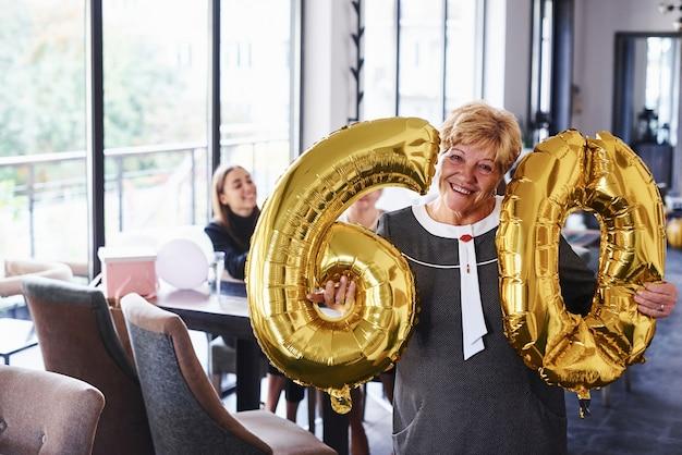 Z balonami z numerem 60 w rękach. starsza kobieta z rodziną i przyjaciółmi świętuje urodziny w pomieszczeniu.