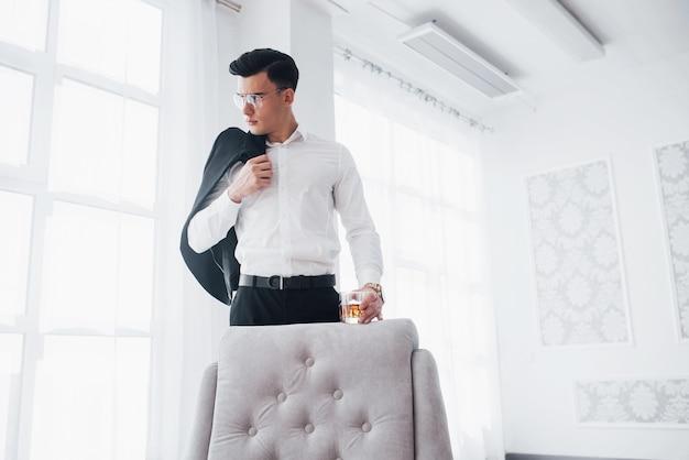 Z białym krzesłem z przodu. luksusowo wyglądający mężczyzna w klasycznym stroju stoi w pokoju i trzyma górę garnituru i szklankę z alkoholem.